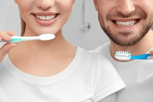 young happy couple brushing teeth in bathroom-img-blog