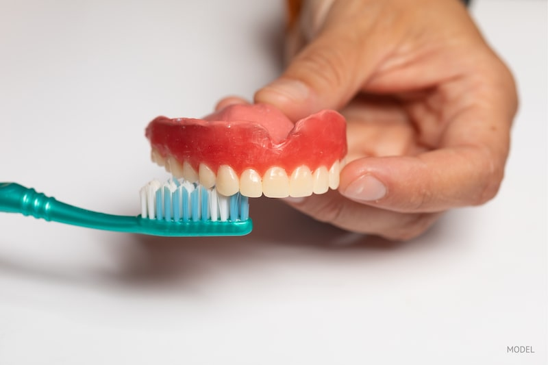 Close-up image of a person brushing their dentures with a toothbrush.
